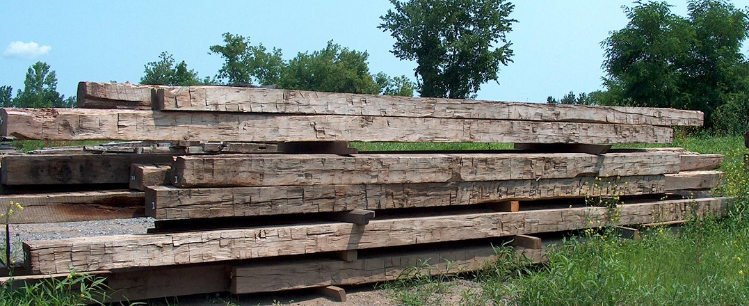 A stack of hand hewn timbers wait in our yard for the next big project.