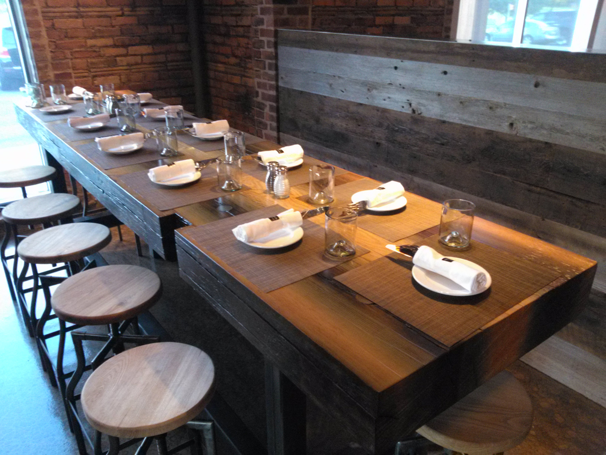 Reclaimed from a canal lock, tha massive reclaimed Douglas fir timber was sawn into slabs to from community tables at TRATA in Rochester, NY.