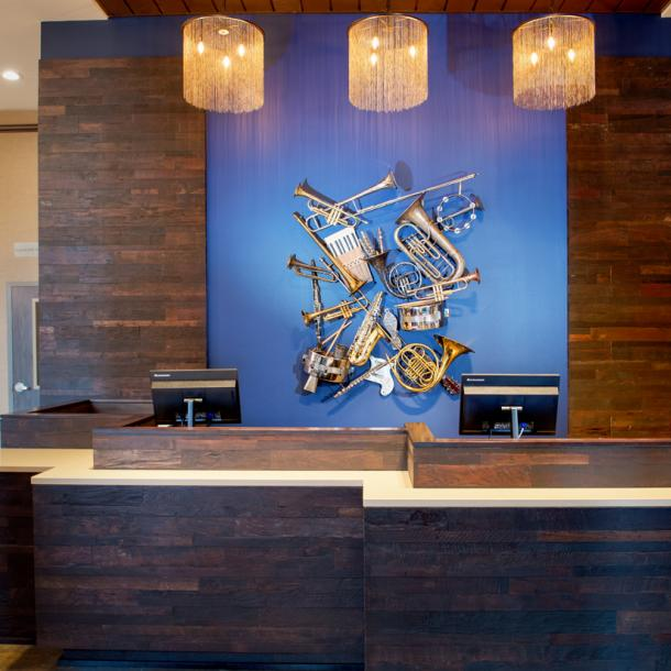 Reclaimed Teak with a custom finish wraps around the hotel lobby front desk area