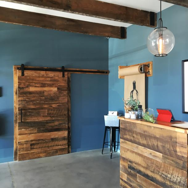 A flat track door and hostess station were made with Settlers' Plank reclaimed hardwoods by NEWwoodworks.