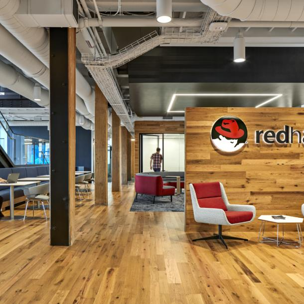 The American Gothic Oak flooring and paneling contrasts well with the branded colors of Red Hat in Boston, MA.