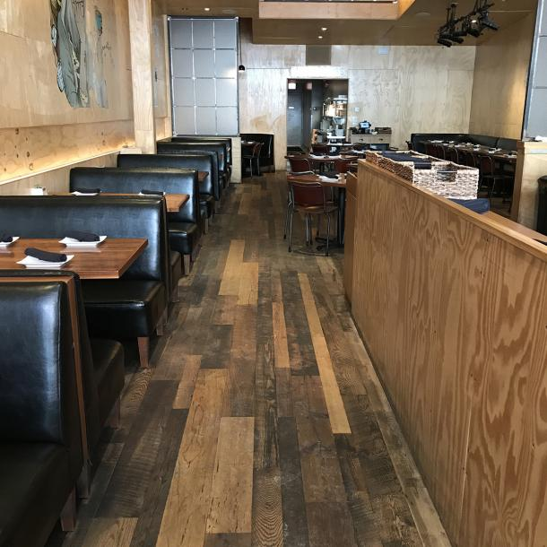 The flooring at Umami Burger in Chicago, IL made up of reclaimed Settlers' Plank Mixed hardwoods.
