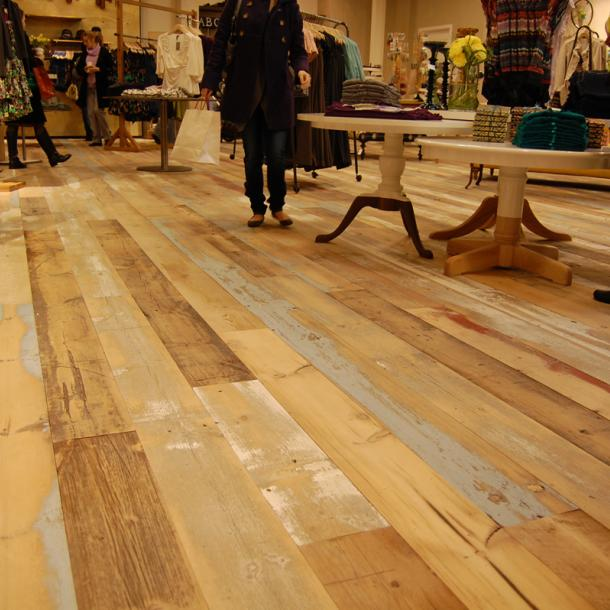 A custom mixture of American Prairie reclaimed softwoods (barn wood) was gently planed to keep some of the paint intact for this custom wide plank floor.