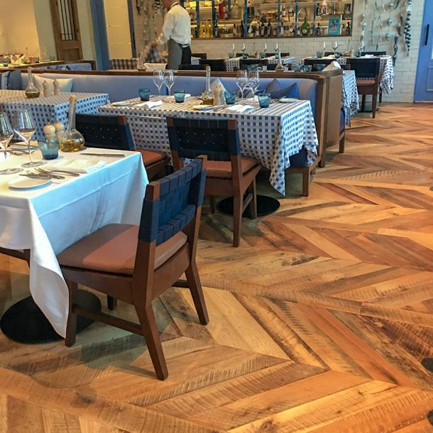 Pioneer Millworks reclaimed Settlers' Plank Mixed Hardwoods in Dolce Riviera restaurant in Dallas, Texas. Installed in a chevron pattern.