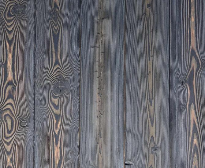 Shou Sugi Ban Larch Cinder by Pioneer Millworks. Charred wood siding and paneling that is burned, brushed twice, and coated with an exterior oil